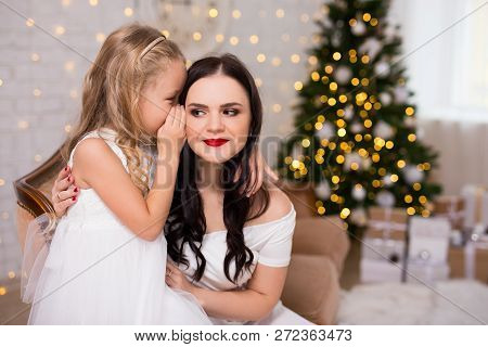 Portrait Of Happy Daughter Whispering Secret Or Christmas Gift Wishes To Her Mother In Decorated Liv