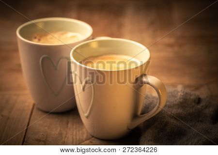 Two Mugs Decorated With The Outline Of A Heart With Hot Steaming Frothy Coffee On A Rustic Wood Tabl