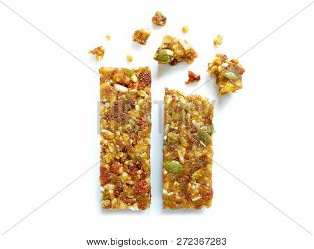 Whole Wheat Cereal Bars Or Flapjacks With Pumpkin Seeds And Dried Fruit With Crumbs Isolated On Whit