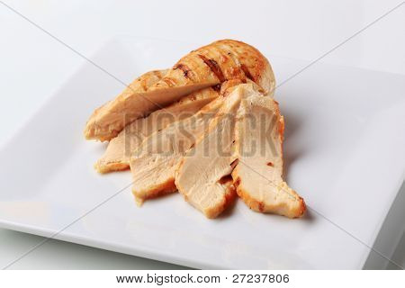Sliced grilled-roasted schnitzel on a white plate, studio shoot