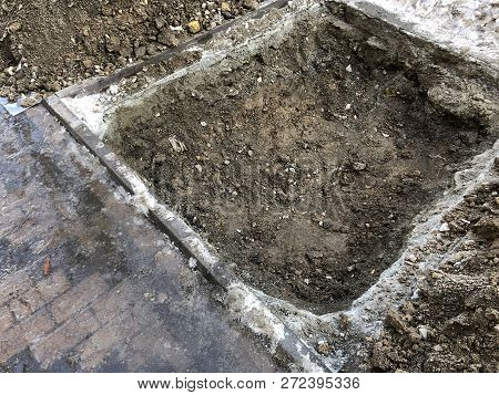 A Square Pit With The Ground From It Excavated In The Asphalt. Digging Holes On The Ground During Ro