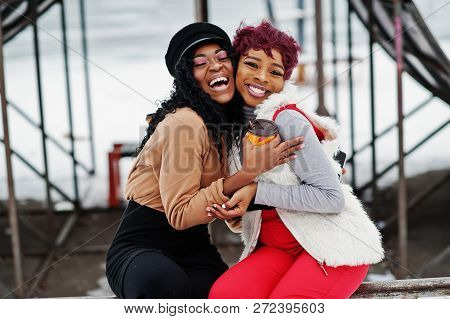 Two African American Womans Posed At Winter Day Against Snowy Background With Cups Of Coffee.
