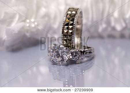 Diamond ring with wedding band set against a white garter and reflective surface