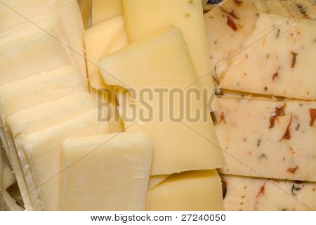 Small slices of pepper cheese, swiss cheese and mozzarella cheese prepared as appetizers.