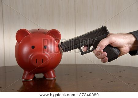A man ready to take out his broke piggy bank with a loaded pistol.