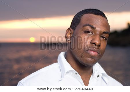 An African American man poses for a photo along the ocean edge.