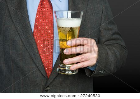 A businessman with a cold pilsner glass full of beer.