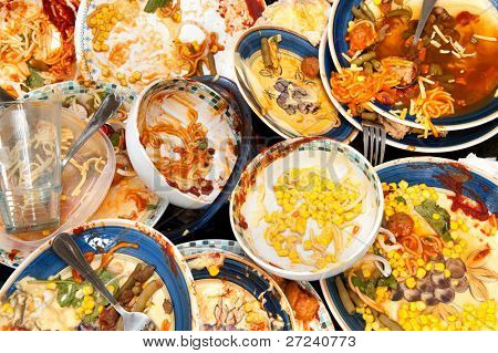 A mass of dirty, filthy dishes with food scraps waiting to be washed. poster