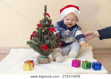 Mom holds the hand of a disgruntled funny kid in a Santa hat poster