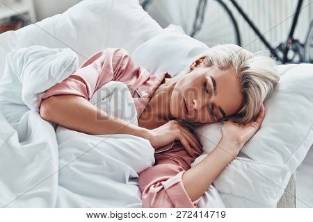 Just One More Minute In Bed. Top View Of Attractive Young Woman Sleeping While Lying In Bed At Home