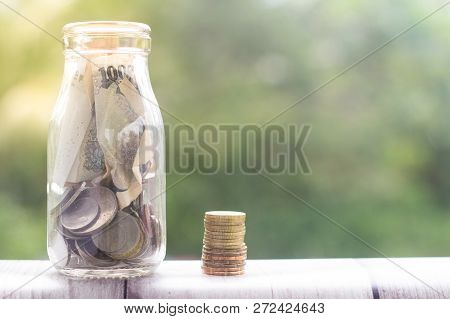 Stack Of Coins Beside A Glass Jar Filled With Money. Conceptual.