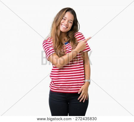 Young beautiful brunette woman wearing stripes t-shirt over isolated background cheerful with a smile of face pointing with hand and finger up to the side with happy and natural expression on face