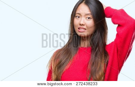 Young asian woman wearing winter sweater over isolated background confuse and wonder about question. Uncertain with doubt, thinking with hand on head. Pensive concept.