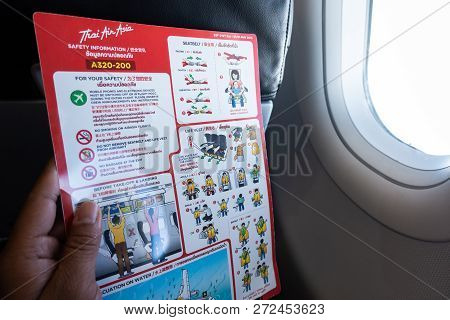 Bangkok, Thailand - November 20, 2018: Asian Man Read Flight Safety Instructions On Card Board Fligh
