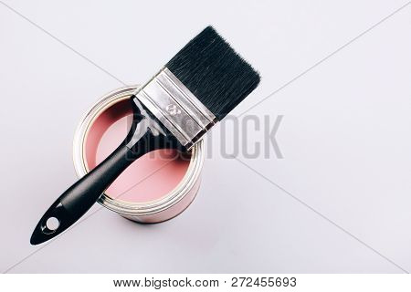Brush With Black Handle On Open Can Of Pink Paint On Grey Background. Renovation Concept. Vertical P