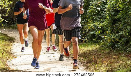 A Group Of High School Runners Are Training Together On A Dirt Path On A Sunny Afternoon, Running To