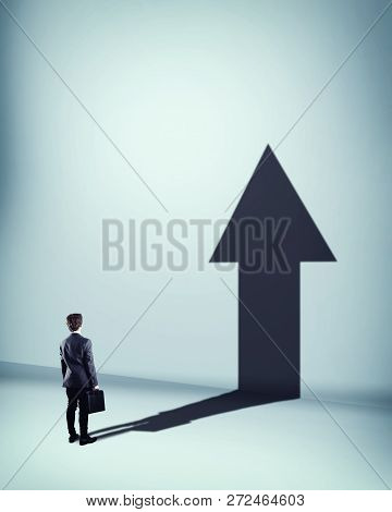Businessman Standing In Front Of Wall And Hist Shadow Is Shaped As An Arrow. The Concept Of Personal