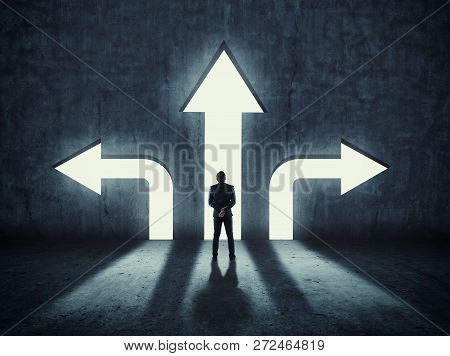 Businessman Having To Choose Between Three Different Arrows Pointing In Opposite Direction. The Conc