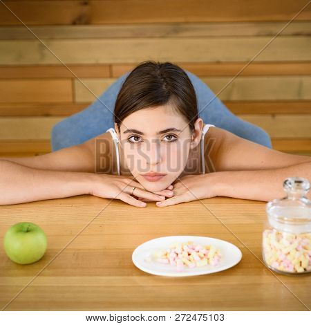 Trying To Make A Right Choice. Pretty Woman Look At Apple And Marshmallows. Woman Choose What Food T