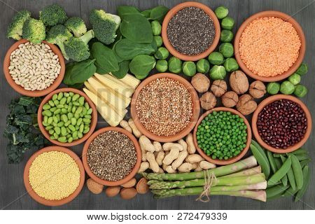 High protein source health food with fresh vegetables, legumes, nuts, grains and seeds, high in dietary fibre, antioxidants, anthocaynins and vitamins. Top view on rustic wood background.