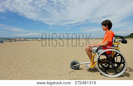 Boy With Orange T-shirt Sitting On The Special Wheelchair With Aluminum Alloy Wheels To Move On The