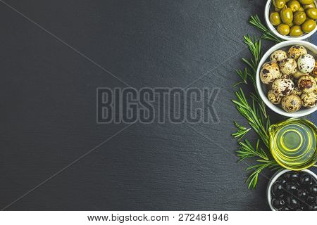 Set Of Black And Green Olives, Quail Eggs On Plates, Olive Oil And Rosemary, On A Black Stone Backgr