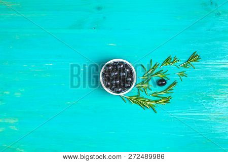 Set Of Black Olives On Plate And Rosemary On A Blue Turquoise Wooden Table Background. Top View, Cop