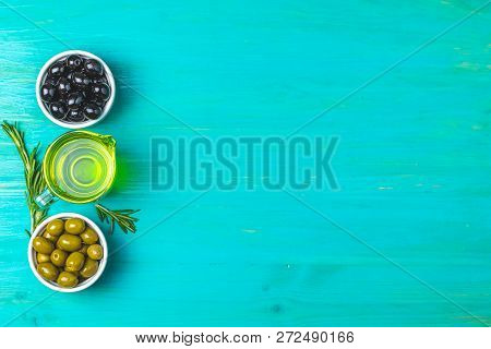 Set Of Black And Green Olives On Plates, Olive Oil And Rosemary, On A Blue Turquoise Wooden Table Ba