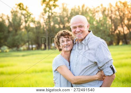 Attractive Smiling Mature couple portrait outdoors. Senior husband and wife in their 50s enjoying the success and prosperity of life