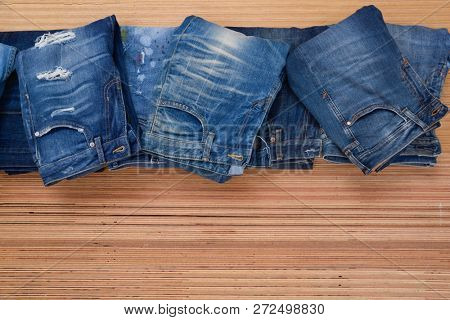 Pile of Jeans. Stylish clothes. Selective focus on wooden background