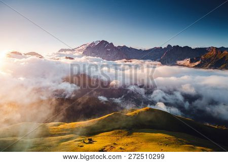 Thick fog covered the ridge in morning. Location place Val di Fassa valley. Scenic image of famous glacier Marmolada, passo Sella, Dolomiti, South Tyrol, Italy, Europe. Discover the beauty of world.