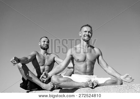 Reach balance by virtue of yoga. Sport and health care. Daily exercises to maintain health. Health and yoga practice. Towards health. Men practice yoga outdoors. Muscular men training on fresh air. poster