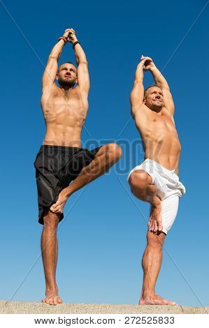 Men Practice Yoga Outdoors. Muscular Men Training On Fresh Air. Reach Balance By Virtue Of Yoga. Spo