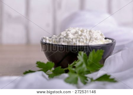 A Fresh Ricotta Cheese With Parsley Leaf On White Marble Table