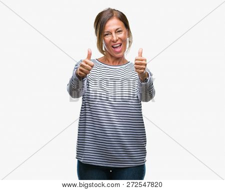 Middle age senior hispanic woman over isolated background approving doing positive gesture with hand, thumbs up smiling and happy for success. Looking at the camera, winner gesture.