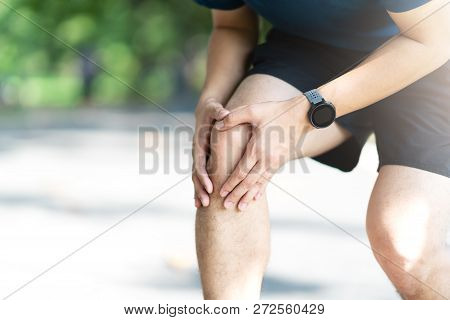 Young Asian Sporty Man Holding Knee Pain In Running Public Nature Park In The Morning. Joint Or Leg