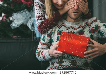 Young Woman Is Giving A Christmas Gift To Her Surprised Beloved Man Near The Fir Tree And Wearing Ch
