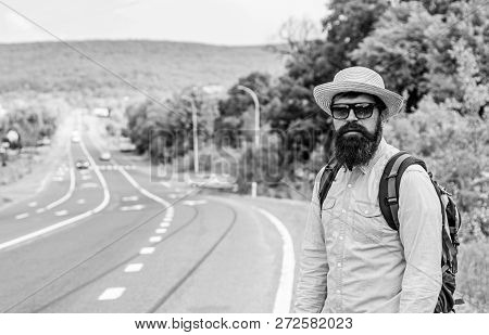 Man At Edge Of Highway Looking For Transport. On The Road. Hitchhiking Means Transportation That Gai