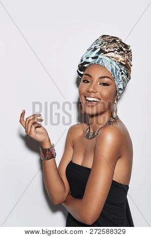 African Beauty. Attractive Young African Woman In Turban Looking At Camera And Smiling While Standin