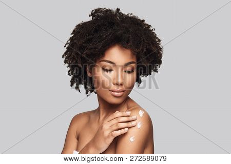 Skin Moisturizer. Attractive Young African Woman Applying Body Cream And Smiling While Standing Agai