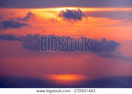 Sunset cloudy sky over ocean water. Amazing landscape in bright scarlet, blue tints. Bright sky with dense clouds over water surface. Sun lights reflection. Beauty of wild untouched nature.