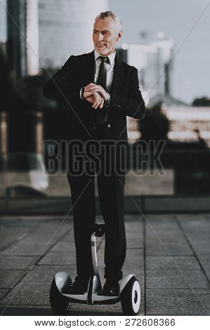 Businessman Is Riding On Gyroboard. Businessman Is Looking A Time On Clock. Businessman Is Old Smili