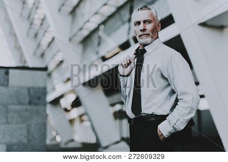 Businessman Is Holding A Jacket. Businessman Is Old Serious Man. Man Wearing In Black Suit. Man Is L