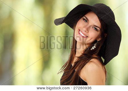 summer teen girl cheerful in panama and  sunglasses enjoying over green nature background