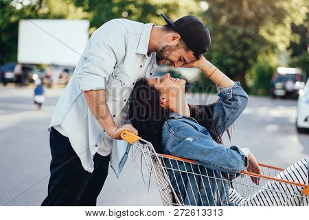 Handsome Guy Carries His Girlfriend In Cart. Guy Kisses His Girlfriend