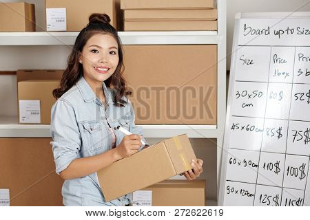 Smiling Delivery Service Worker Counting Shipment Cost And Writing It Down
