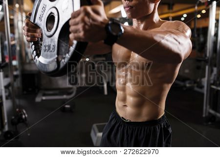 Sweaty Young Man Doing Exercies For Arms And Chest In Gym
