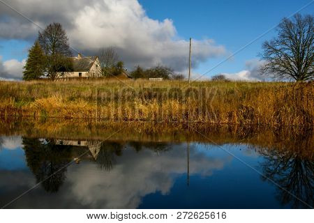 View On Autumn Landscape Of River And Trees In Sunny Day. Grass On River Coast In Autumn Day. Reflec