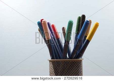 Basket With Makers Pens In A Light Blue Background