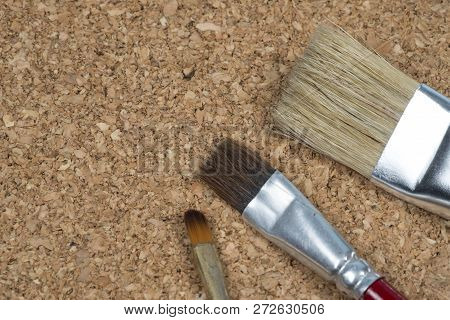 Tip Of Paint Brushes On A Cork Background.